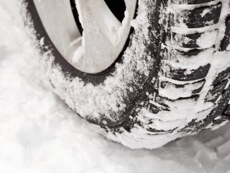 Car tire on snowy road close up photo