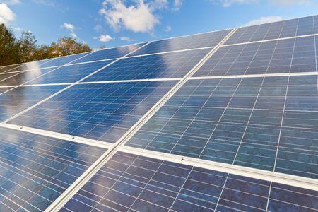 Die Photovoltaik-Panels für erneuerbare Energieerzeugung mit blauem Himmel und Wolken