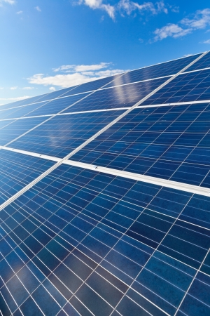 cobradores: Solar fotovoltaica paneles de campo para la producci�n de energ�a renovable con el cielo azul y las nubes Foto de archivo