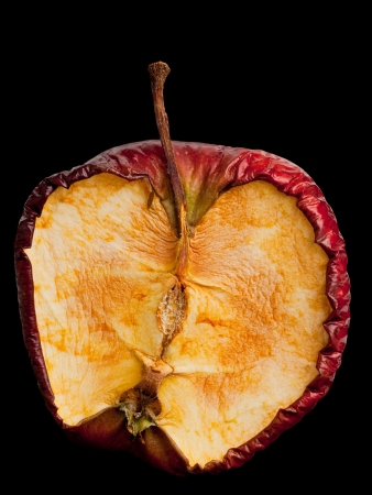 Half old dry rotten red apple isolated on black background photo