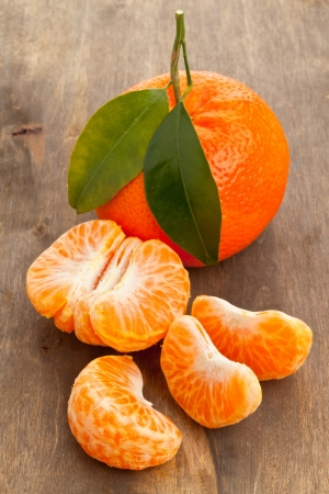 Organic mandarin whole and slices on wooden table Stock Photo