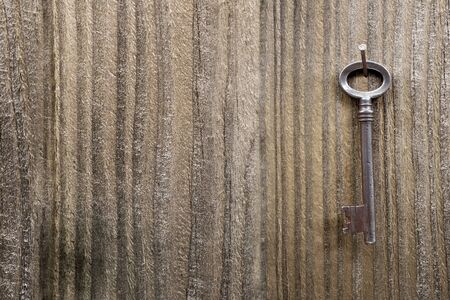 Old vintage metal key hanging on wooden wall Stock Photo - 17782742