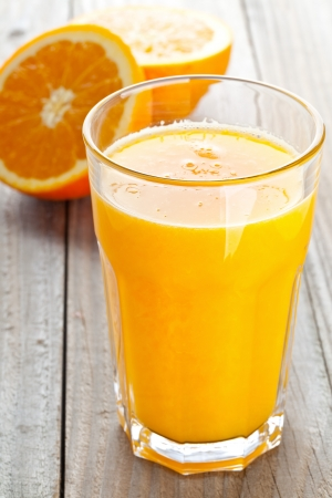 Glass of freshly pressed orange juice with sliced orange half on wooden table Stock Photo - 17782732