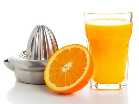 Glass of freshly pressed orange juice with sliced orange half and juice squeezer over white background