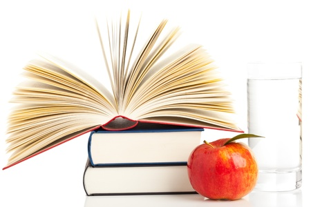 stacked books: Open book on stack of books with apple and glass of water - education and nutrition concept Stock Photo