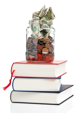 Books with penny jar filled with coins and banknotes - tuition or education financing concept Archivio Fotografico