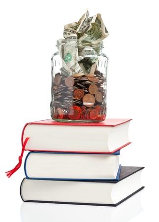 Livres avec pot sou rempli de pièces et billets - concept financement des frais de scolarité ou d'éducation Banque d'images