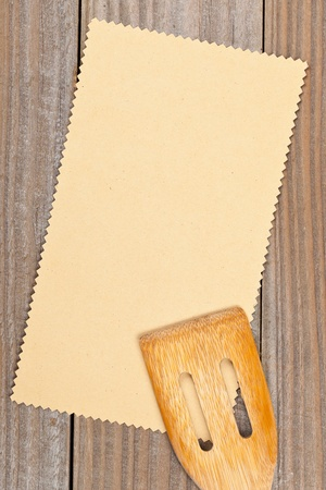 Empty paper for recipe with wooden cooking utensils on kitchen table photo