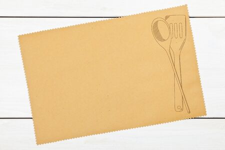 Empty paper for recipe with drawn cooking utensils on kitchen table photo