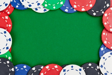 Different casino chips frame on green table background with copyspace photo