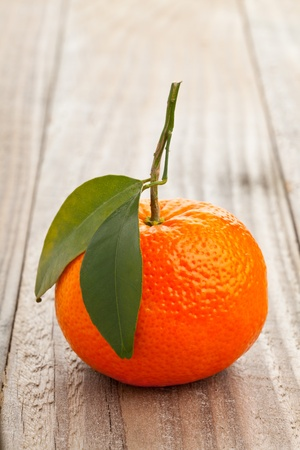 Single whole organic tangerine wit green leaves on wooden table Stock Photo - 19424097