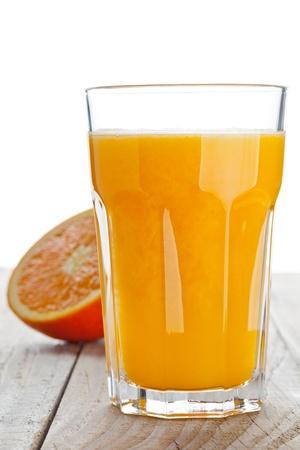 Glass of freshly pressed orange juice with sliced orange half on wooden table Stock Photo - 19424090