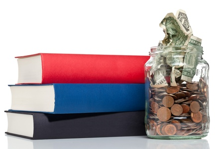 Books with penny jar filled with coins and banknotes - tuition or education financing concept Stock Photo