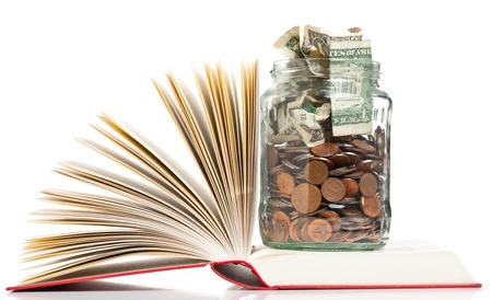penny: Books with penny jar filled with coins and banknotes - tuition or education financing concept Stock Photo