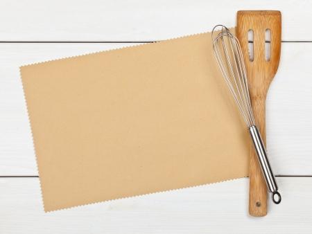 kitchen utensils: Papel vac�o para la receta con utensilios de cocina en la mesa de la cocina Foto de archivo