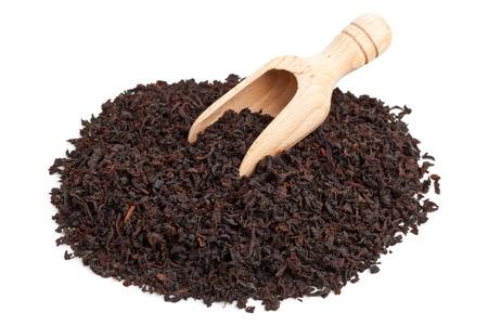Ceylon black tea crop in wooden scoop over white background