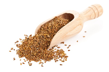 Anise seed in wooden scoop over white background