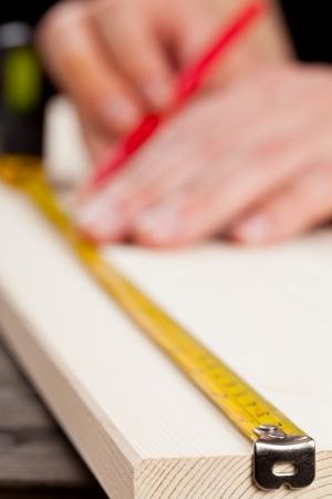 Jeune homme mesurant planche en bois - bricolage ou un concept de rénovation maison Banque d'images