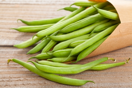 Organic pole beans in paper bag on wooden table Stock Photo - 21580545