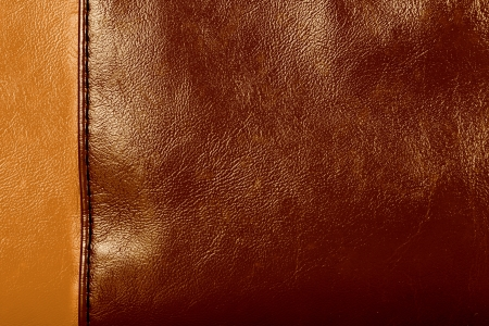 Light and dark brown colored stitched leather close up with seam