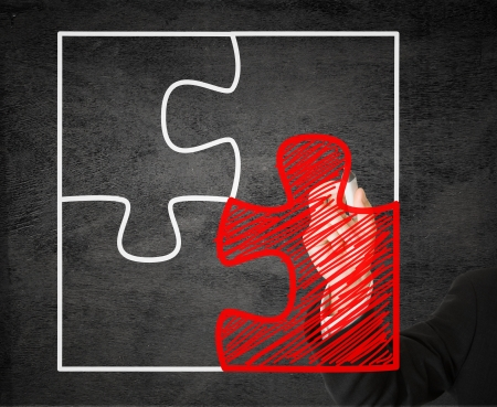 Business man drawing missing jigsaw puzzle piece on transparent drawing board - solution or teamwork concept photo