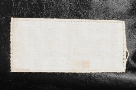 Blank fabric label on leather background close up photo