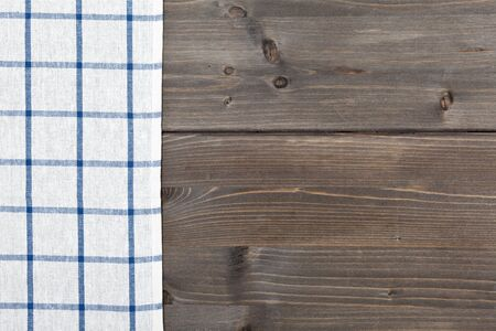 checker: Blue checker tablecloth on brown vintage wooden table background Stock Photo