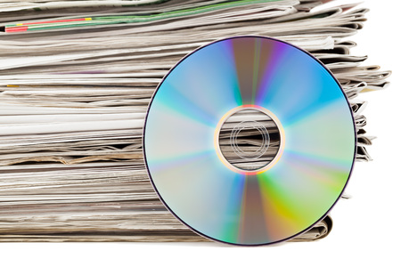 Stack of newspapers with CD - electronic media concept photo