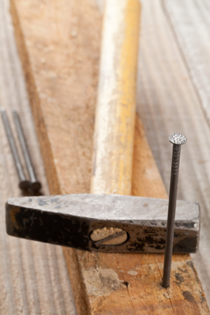 doityourself: Hammer and nail with selective focus on the head of the nail - woodworking or do-it-yourself concept