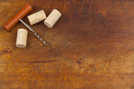 Corkscrew and wine corks on wooden background photo