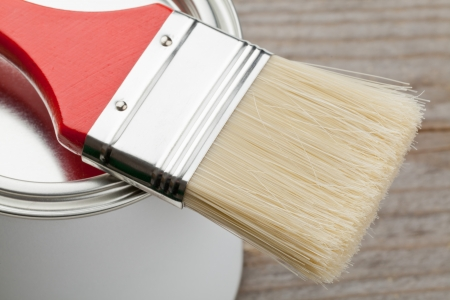 Red paint brush on paint can on wooden plank - home renovation or diy concept photo