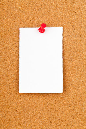 Blank white paper note with red pin on corkboard photo