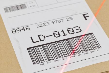 Barcode op de scheepvaart etiket op doos gescand door automatische laserscanner Stockfoto