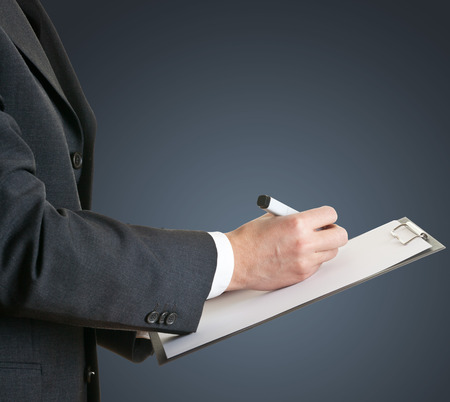 Businessman takes notes on clipboard with copyspace photo