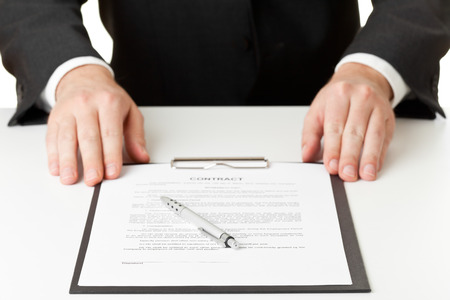Businessman with contract on clipboard and pen for signature