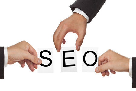 Hands holding cards with the letters SEO - Search Engine Optimization photo