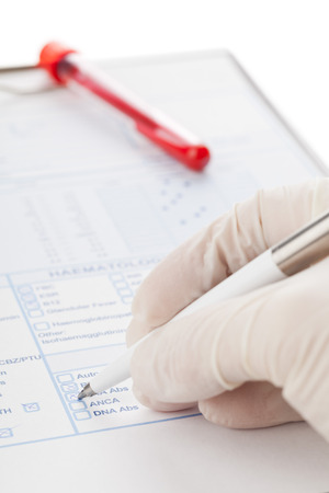 specimen: Doctor filling out blood test form with blood sample vial in the background Stock Photo
