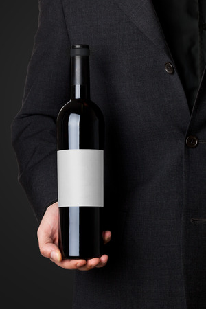 alcohol bottles: Man in suit holding red wine bottle isolated on black background