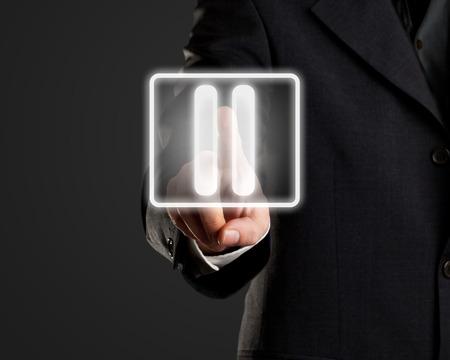 Businessman pressing pause button on virtual screen