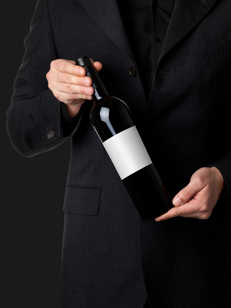 Man in suit holding red wine bottle isolated on black  photo