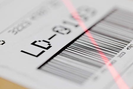 Barcode on shipping label on box scanned by automatic laser scanner photo