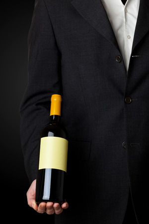 Man in suit holding white wine bottle isolated on black background photo