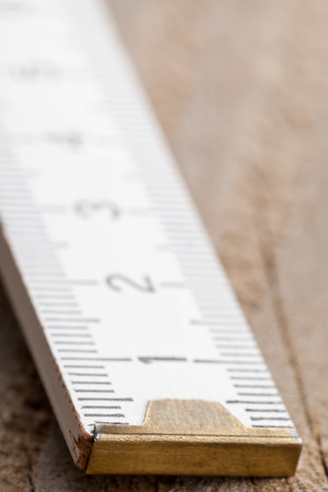 Macro shot of folding rule on wooden background with selective focus Stock Photo