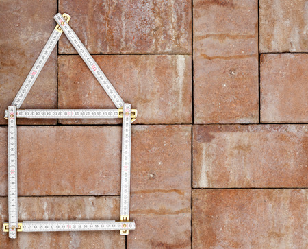 Folding rule forming the shape of a house on brick background background