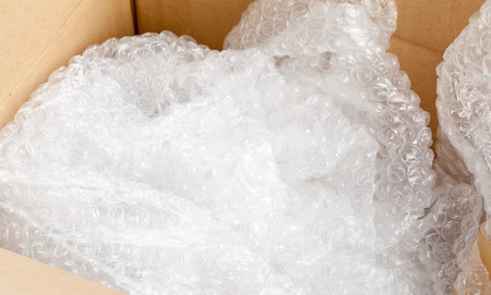 Used bubble wrap plastic in brown carton box - packaging or moving concept