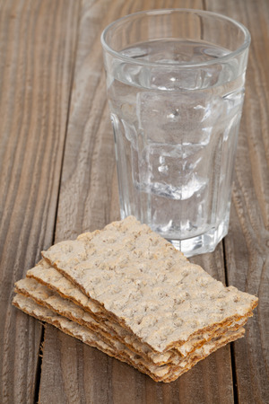 Stacked slices of wheat crispbread with glass of water on wooden table - dieting concept