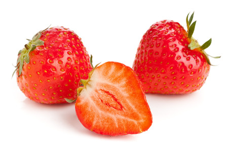 Organic ripe strawberries cut and whole over white background photo