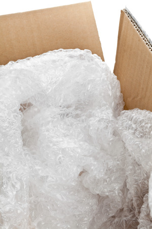 packing supplies: Used bubble plastic in brown carton box - packaging or moving concept Stock Photo