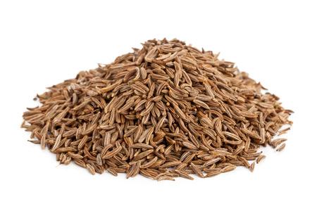 白い背景の上の乾燥クミンまたはキャラウェー種のヒープ