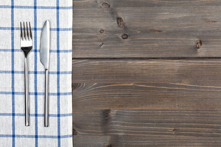 checker: Blue checker tablecloth on brown vintage wooden table background with silverware
